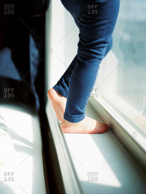 Child standing on windowsill - Offset