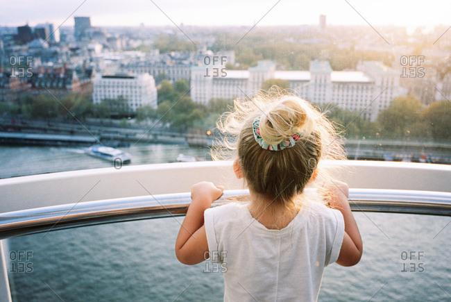 Little blonde girl over railing at river