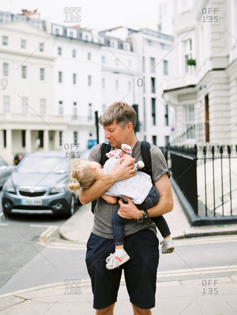 Father carrying little girl in arms on city street