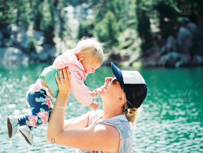 Mother holding baby girl in the air by lake