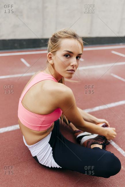 Blonde sportswoman resting on the track