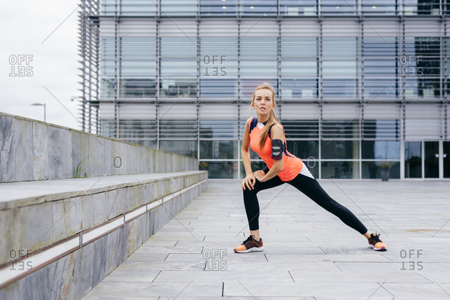 Pretty blonde girl doing stretching on the street before running