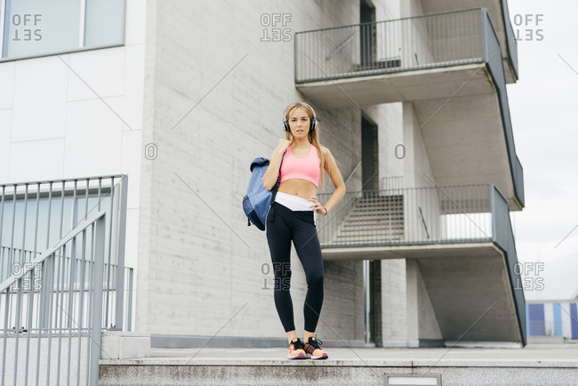 Attractive sportswoman standing and listening music on headphones on the street