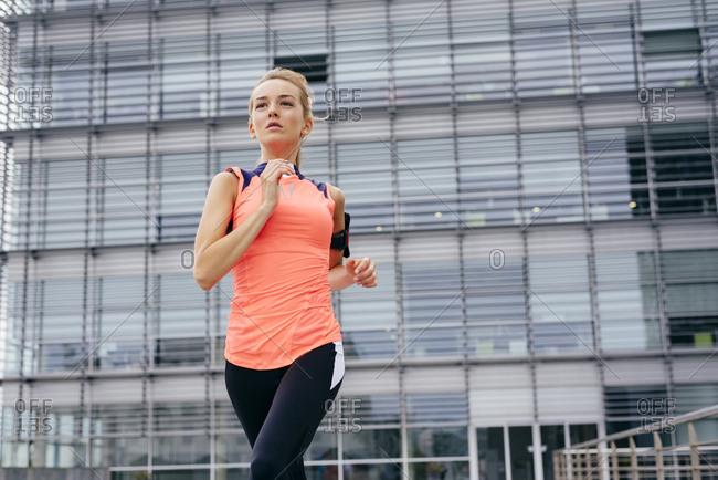 Pretty blonde girl jogging on the street