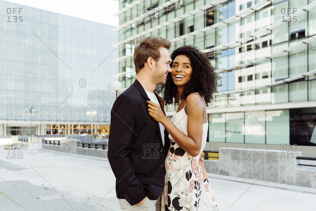 Pretty black woman and caucasian man smiling and holding hands while walking on city street together on sunny day