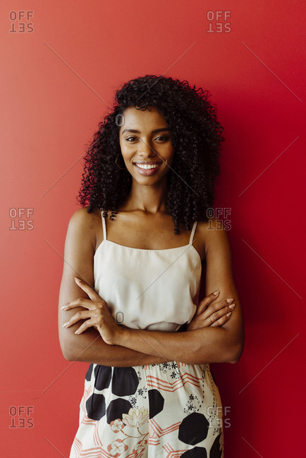 Attractive african-american woman in elegant outfit smiling and looking at camera while keeping arms folded and standing on red background