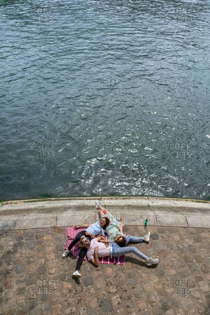 Friends lying on blanket on waterfront