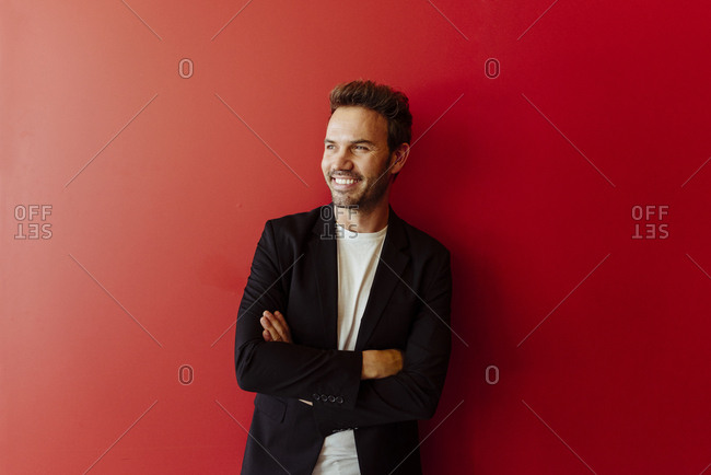 Handsome young man in elegant outfit smiling and looking at camera while standing on bright red background