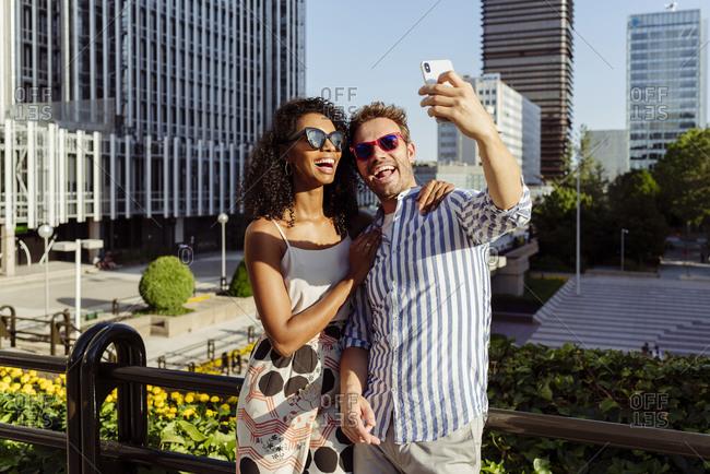 Beautiful black woman and handsome caucasian man posing for selfie while standing on background of modern city