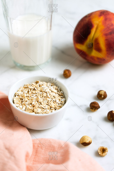 Oat bowl with hazelnuts, a glass of milk and a peach