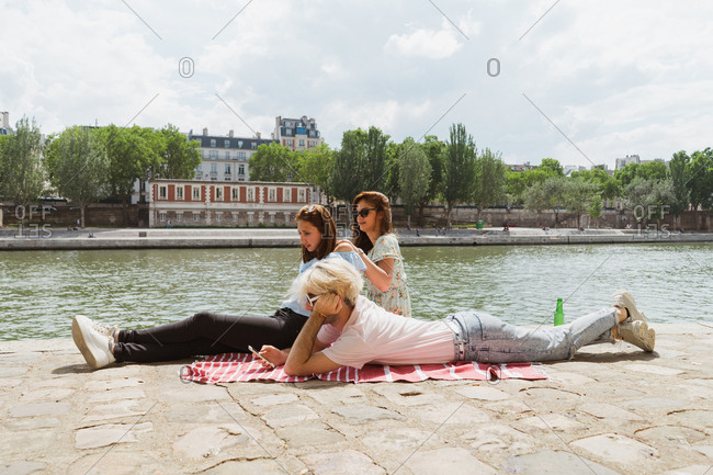 Smiling friends relaxing on waterfront