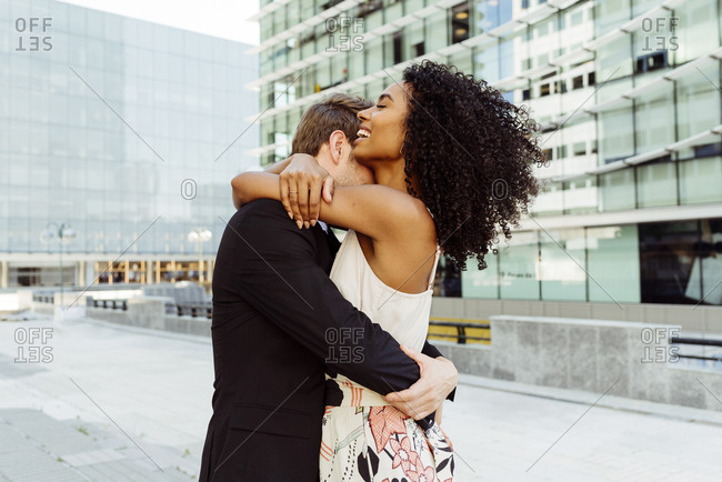 Side view of attractive black woman smiling and embracing caucasian man while standing on city street together