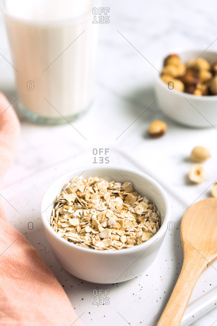 Oat bowl with a glass of milk and hazelnuts