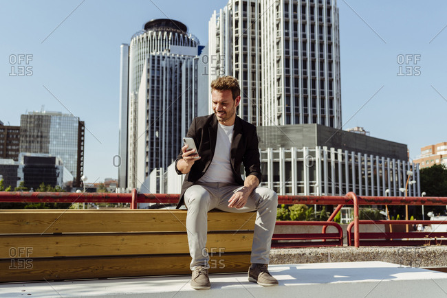 Handsome guy smiling and browsing smartphone while sitting on bench on street of modern city
