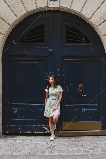 Pensive female in beautiful dress with floral print leaning on shabby door and looking away