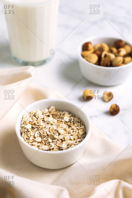 Oat bowl with hazelnuts and a glass of milk