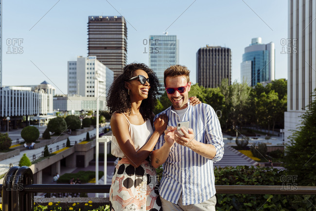 Beautiful black woman and handsome caucasian man using smartphone while standing on background of modern city
