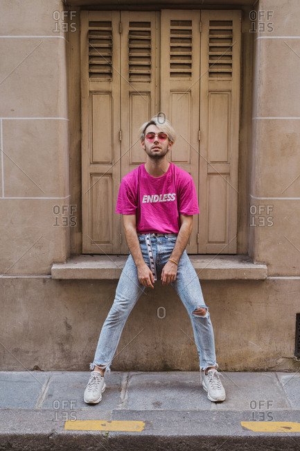 Trendy male with fashion hairstyle in bright casual clothes and pink sunglasses leaning on sill of window with closed sashes and looking at camera