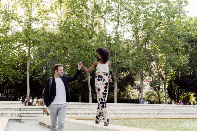 Charming black woman smiling and walking on fountain border near boyfriend while spending time in park together
