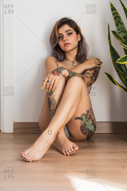 Attractive inked woman sitting on floor and looking at camera