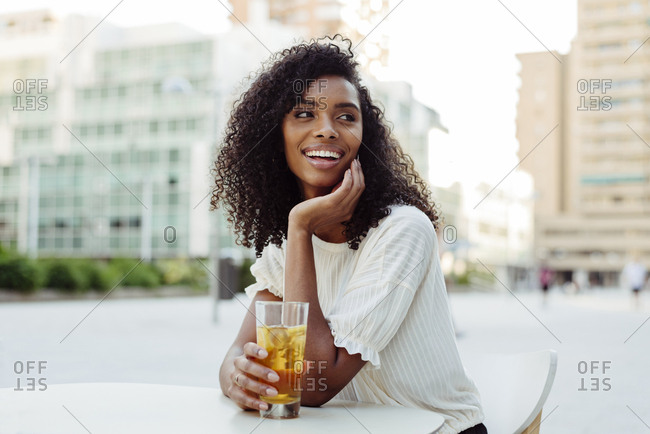 Charming african-american woman smiling and looking away while holding glass of tasty beverage and leaning on table in outdoor cafe