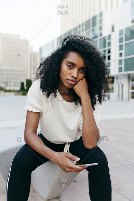 Young african-american woman rubbing temple and using smartphone while sitting on street of modern city