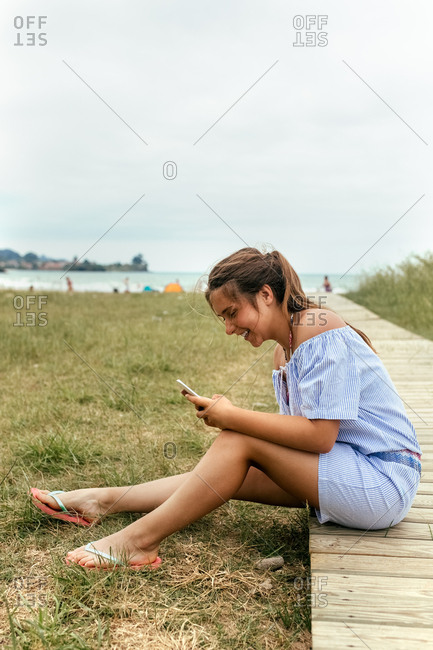 Portrait of a teenage girl using her smartphone on the beach