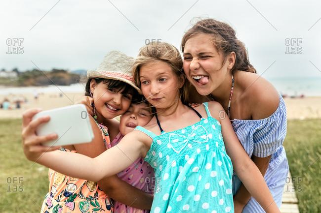 Four little friends making a selfie on the beach