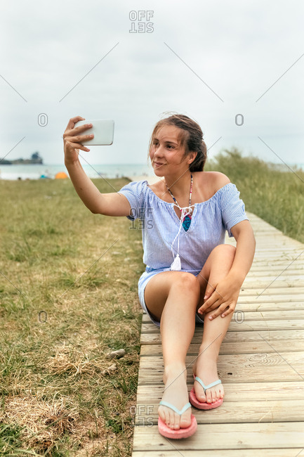 Portrait of a teenage girl making a selfie with her smartphone on the beach