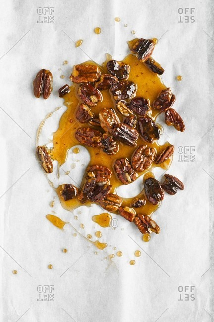 Pecan nut brittle on a white baking parchment (seen from above)
