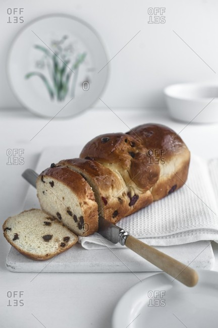 A fruit loaf, sliced, on a white chopping board with a knife and a cloth