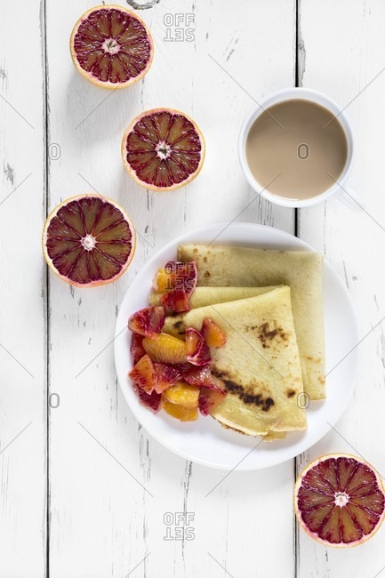 Crepes with blood oranges on a plate with a cup of coffee and halved blood oranges next to it