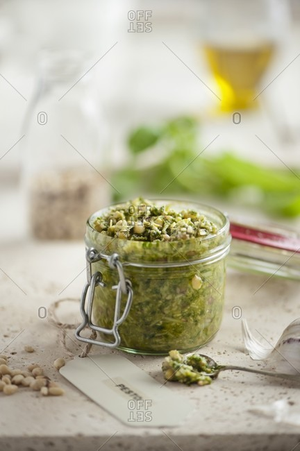 An open jar of fresh basil pesto surrounded by ingredients