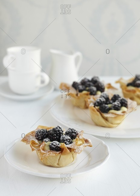 Four filo pastry baskets with vanilla pudding and blueberries