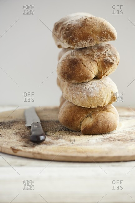 A stack of ciabatta bread on a wooden plate with a bread knife