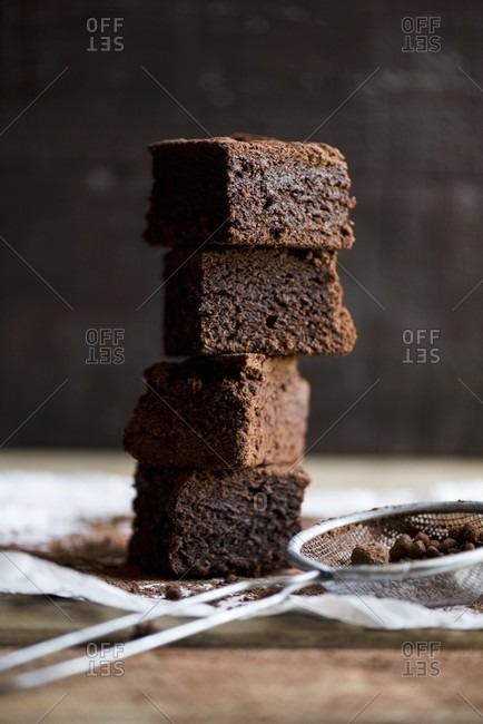 A stack of brownies and a sieve with cocoa powder