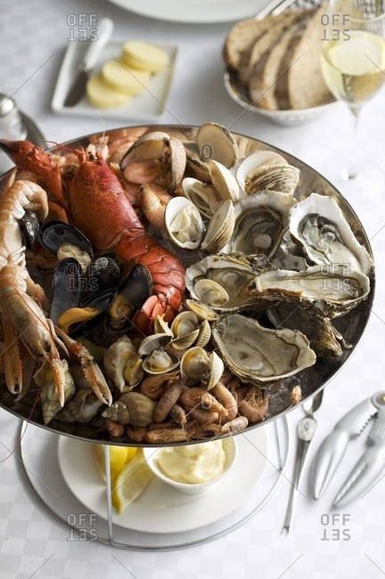 A seafood platter with lobster, oysters, bread, butter and mayonnaise