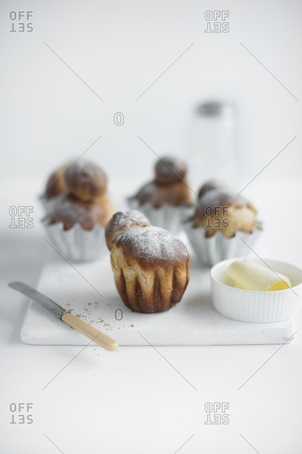 Fresh brioches on a chopping board with butter and a knife