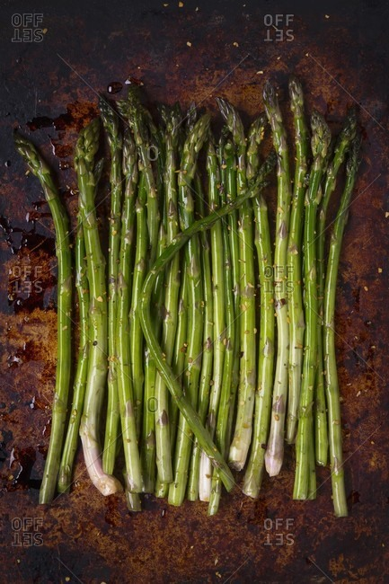 Fresh asparagus with olive oil and spices on a baking tray