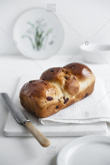 Fruit loaf on a white chopping board with a white kitchen towel