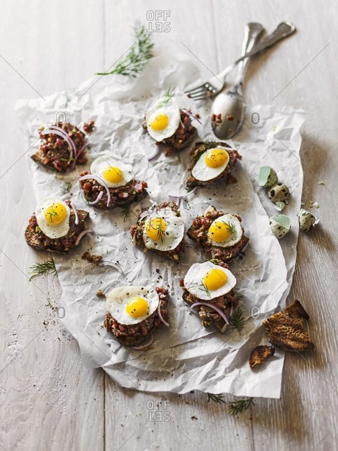 Beef tartare on grilled black bread with fried quail's eggs