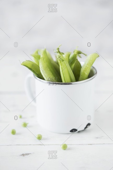 Pea pods in an enamel mug
