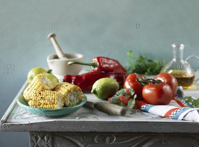 An arrangement featuring grilled corn cobs, tomatoes, peppers, lemons and oil