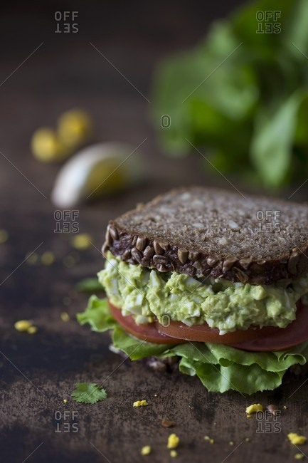 A wholemeal sandwich with avocado and egg salad, and tomatoes