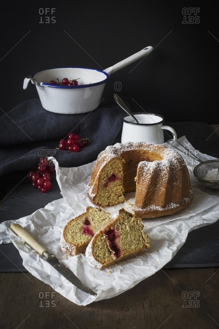 A sliced redcurrant Bundt cake dusted with icing sugar on a piece of white paper on a dark slate surface