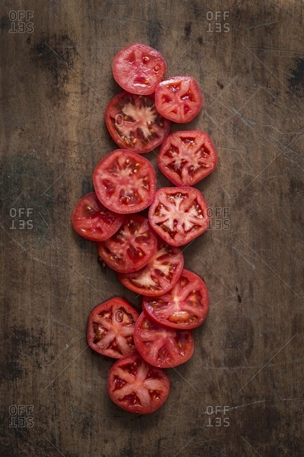 Slices of red tomatoes on a wooden surface (seen from above)