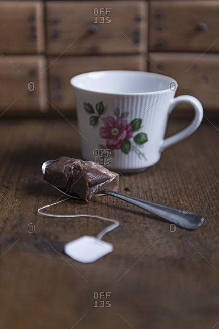 A used tea bag on a spoon and a tea cup with an Eat Frisian tea rose pattern