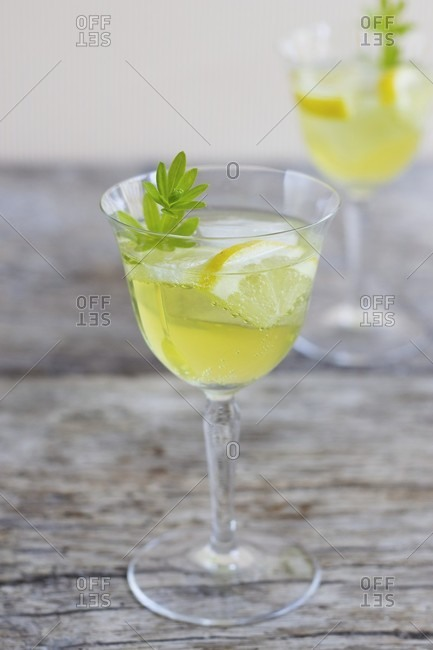 A glass of woodruff punch with ice cubes, lemon and woodruff