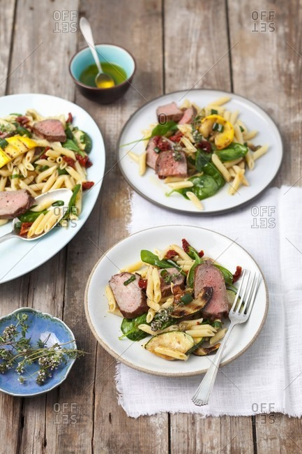 Penne pasta salad with roast beef, courgette, dried tomatoes and spinach