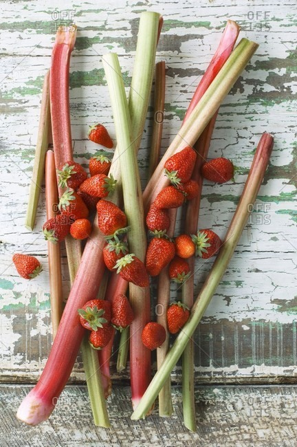 Rhubarb spears and strawberries on a wooden table (seen from above)